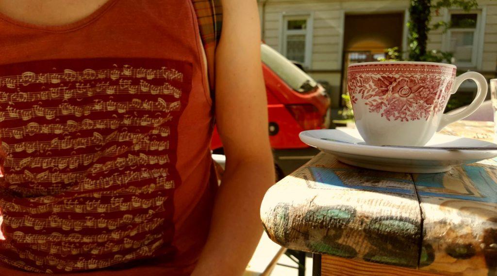 Ein Shirt mit Musiknoten und eine Tasse, die in derselben Farbe gehalten ist: rot